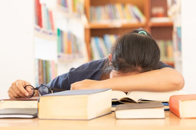 Konzentriertes schülerlesebuch an ihrem schreibtisch in einer bibliothek