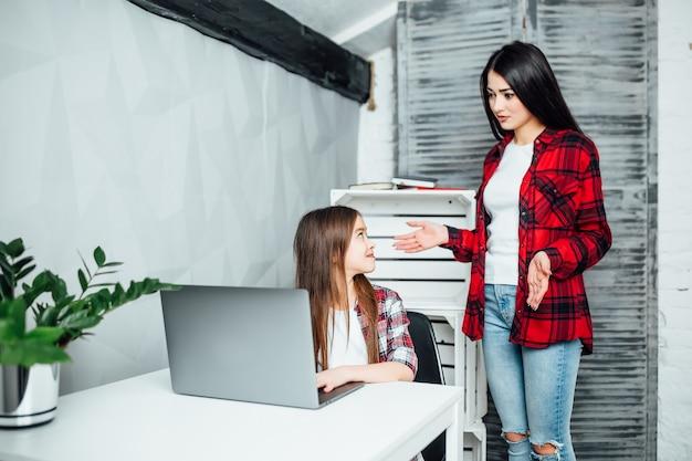 Konzentriertes schulmädchen, das im zimmer sitzt, während es eine übung am laptop macht, ältere schwester, die ihr hilft