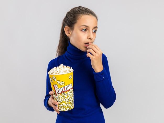 Konzentriertes teenager-mädchen, das einen eimer mit popcorn und popcornstück in der nähe des mundes hält und die seite isoliert auf weißer wand mit kopierraum betrachtet