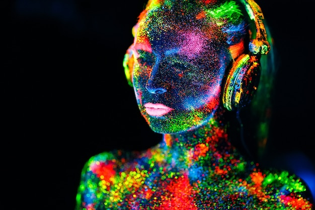 Konzept. auf den körper eines mädchens gemalt dj-deck. halbnacktes mädchen in uv-farben bemalt.
