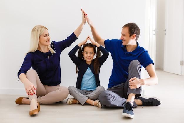 Konzept, das eine junge familie beherbergt. mutter, vater und kind im neuen haus mit dach