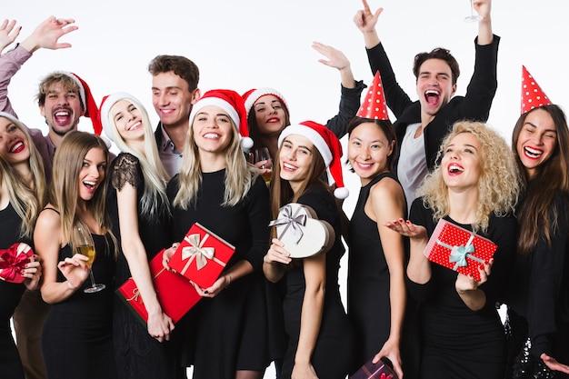 Konzept, das neujahr oder feiertag feiert. gruppe junger schöner leute in stilvoller schwarzer kleidung und weihnachtsmütze mit geschenkboxen in den händen, die spaß haben.
