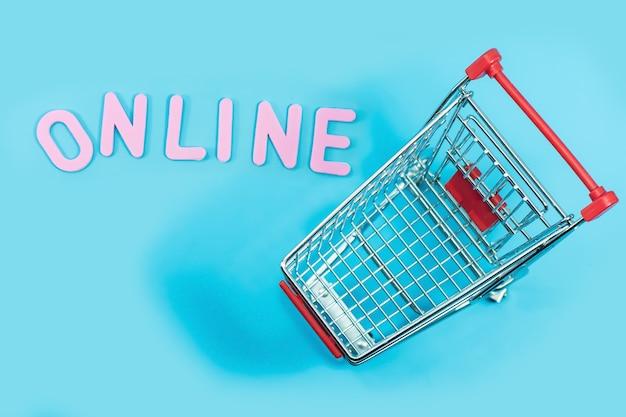 Konzept, das online mit laufkatze auf blau für hintergrund kauft