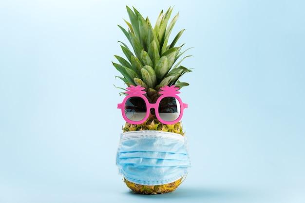 Konzept der ananas bereit für das reisen mit einer maske