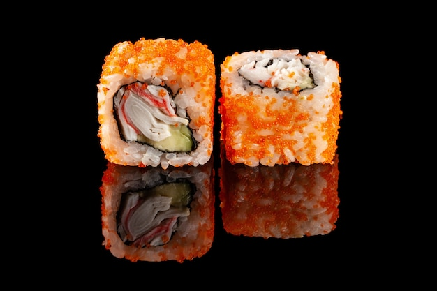 Konzept der asiatischen küche. zwei rollen sushi mit verschiedenen füllungen auf einem schwarzen hintergrund mit dem alter für ein japanisches menü für ein café, restaurant, sushi-bar.