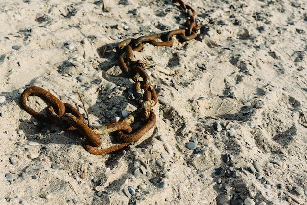 Konzept der aufgabe, der alten rostigen und defekten ketten geworfen in den sand eines schmutzigen strandes.