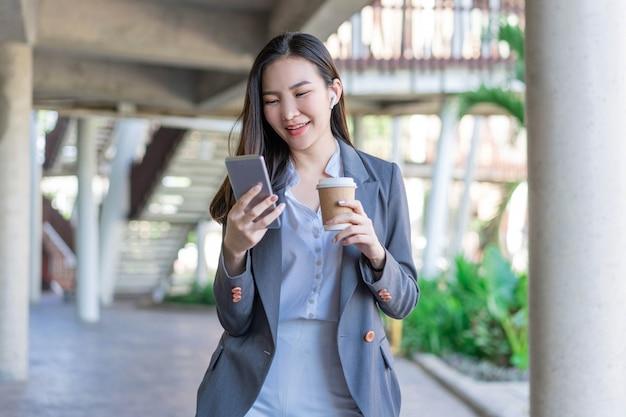 Konzept der berufstätigen frau, eine junge managerin, die eine tasse kaffee hält und mit dem kollegen über den videoanruf kommuniziert.