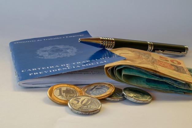 Konzept der beschäftigung und finanzkontrolle mit brasilianischem geld, münzen und banknoten und arbeitskarte.