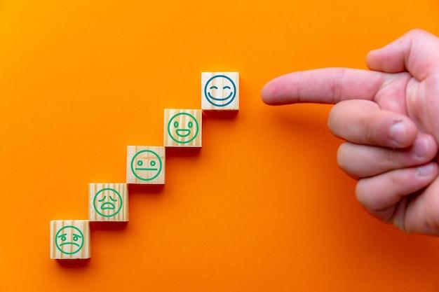 Konzept der bewertung des kundenservice, zufriedenheitsumfrage und höchste bewertung der herausragenden dienstleistungen. auf holzblöcken wählte die hand des kunden das lächelnde gesicht des glücklichen gesichtes aus, kopienraum