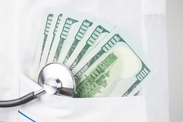 Konzept der bezahlten medizin. arzttasche mit stethoskop und us-dollarnoten.