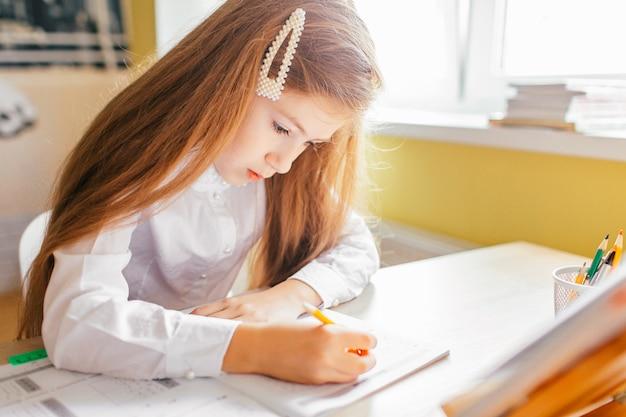 Konzept der bildung zu hause - nettes kleines mädchen mit dem langen haar hausaufgaben auf einer tabelle mit stapel von büchern und von arbeitsbuch studierend oder abschließend