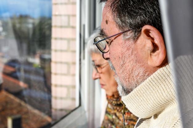 Konzept der coronavirus-quarantäne und der sozialen distanzierung. älteres paar, zu hause mit besorgtem gesichtsausdruck durch das fenster schauend. zu hause bleiben. älterer und pensionierter lebensstil.