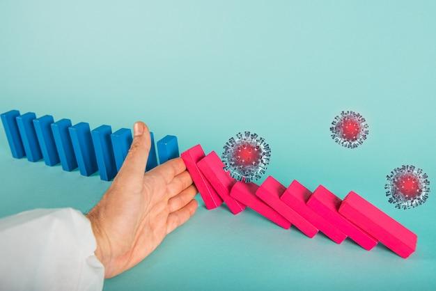 Konzept der covid19 coronavirus-pandemie mit fallender kette wie ein domino-spiel. ansteckung und infektionsverlauf wurden durch die hand eines arztes gestoppt. cyan wand
