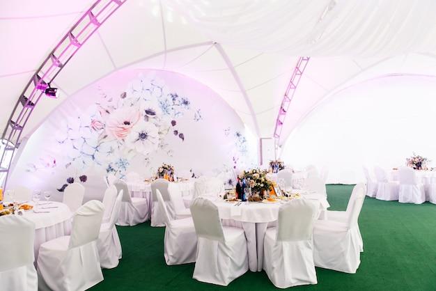 Konzept der dekoration für hochzeit und feier, ein schönes weißes zelt mit blumen für den urlaub dekoriert