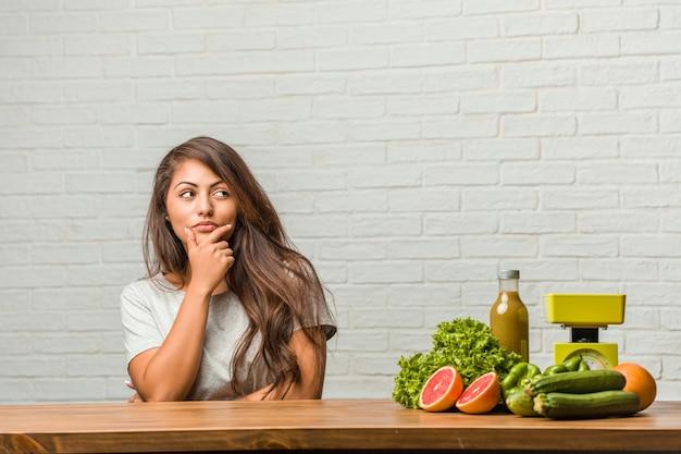 Konzept der diät. porträt einer gesunden jungen lateinischen frau, die oben denkt und schaut
