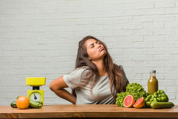 Konzept der diät. porträt einer gesunden jungen lateinischen frau mit den rückseitigen schmerz wegen des arbeitsstresses