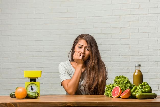 Konzept der diät. porträt von beißenden nägeln einer gesunden jungen lateinischen frau
