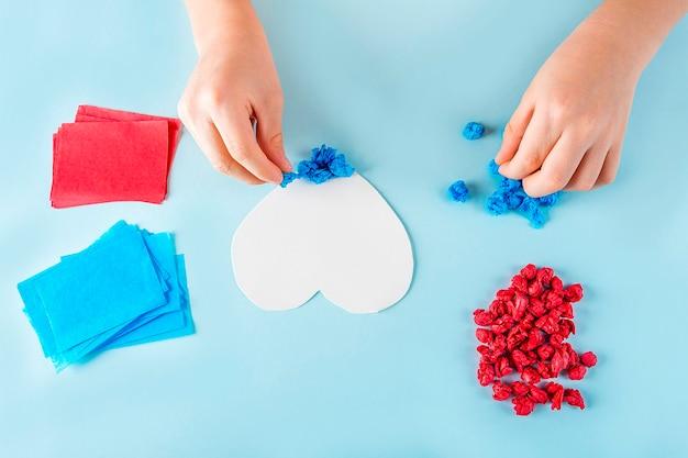 Konzept der diy- und kinderkreativität. kinderhände zerknittern farbige papierstücke. valentinstag handwerk.