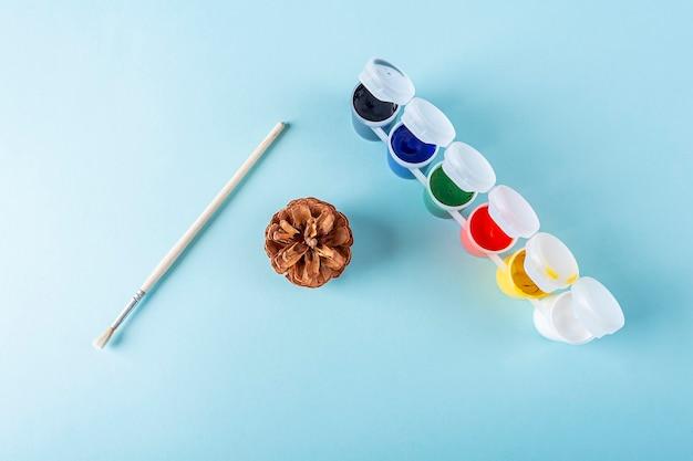 Konzept der diy- und kinderkreativität. schritt für schritt anleitung: tannenzapfen malen. schritt 1 werkzeuge: kegel, pinsel, farbe. kinder weihnachtshandwerk
