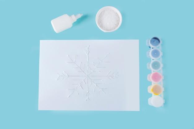 Konzept der diy- und kinderkreativität. schritt für schritt anleitung: wie man schneeflocken aus kleber und salz auf papier macht. schritt 3 kinderhände tragen klebstoff auf die zeichnung auf.