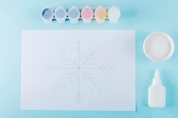 Konzept der diy- und kinderkreativität. schritt für schritt anleitung: wie man schneeflocken mit kleber und salz zeichnet. schritt 2 schneeflockenskizze mit bleistift für kinder