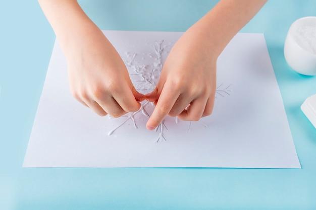 Konzept der diy- und kinderkreativität. schritt für schritt anleitung: wie man schneeflocken mit kleber und salz zeichnet. schritt 4 kinderhände streuen salz auf kleber.