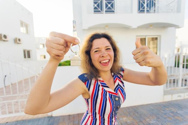 Konzept der einweihung, immobilien, eigentum und umzug - neuer hausbesitzer mit schlüssel.