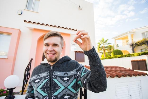 Konzept der einweihungsimmobilie neues zuhause junger mann, der den schlüssel des neuen hauses hält
