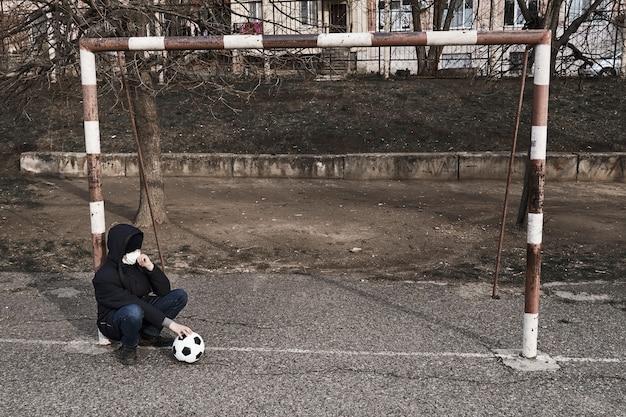 Konzept der epidemie und quarantäne - ein junge mit einer gesichtsmaske und einem ball allein auf dem sportplatz in der stadt