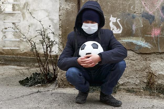 Konzept der epidemie und quarantäne - ein junge mit einer gesichtsmaske und einem ball allein auf der straße in der stadt