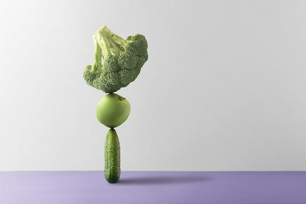 Konzept der ernährungsbilanz. frisches obst und gemüse werden vor einem grauen hintergrund ausbalanciert.