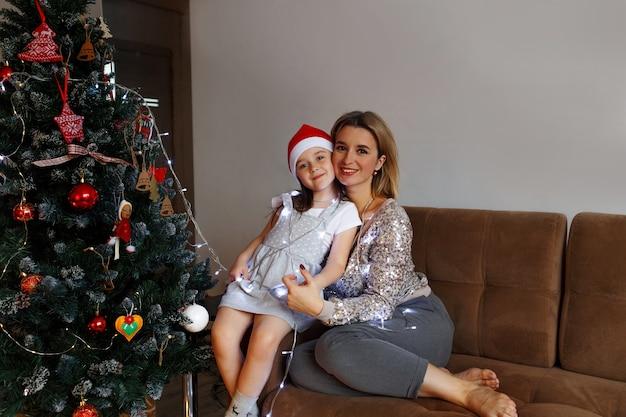 Konzept der familie, weihnachten, feiertage und der menschenglücklichen mutter und der kleinen tochter, die zu hause auf der couch sitzen