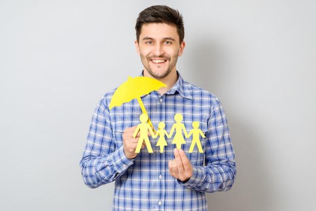 Konzept der familienversicherung mit dem regenschirm, der eine familie schützt