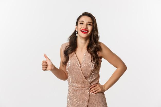 Konzept der feier, feiertage und party. fröhliche elegante frau im abendkleid mit roten lippen, daumen hoch und lachend, genehmigen und mögen etwas gutes
