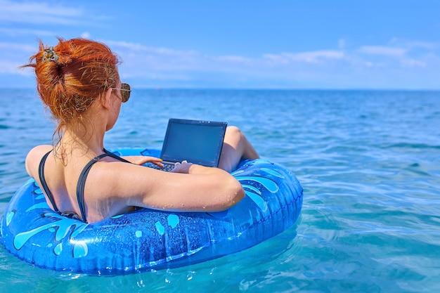 Konzept der fernarbeit. geschäftsfrau, die in einem aufblasbaren ring in meer sitzt