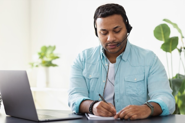 Konzept der fernarbeit. junger indischer mann, support-mitarbeiter oder freiberufler verwendet laptop und headset, um mit dem kunden zu kommunizieren, macht sich notizen in einem notizbuch, online-lernen
