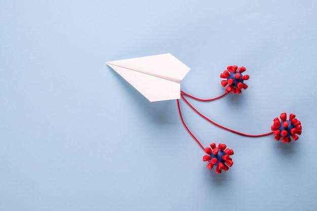 Konzept der fliegengefahr. papierebene und modelle des covid-19-virus