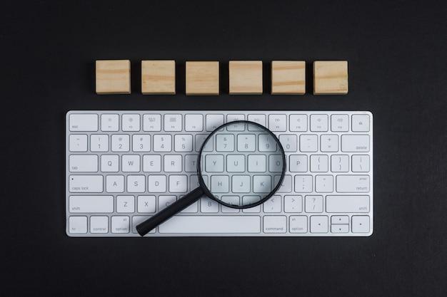 Konzept der forschung mit tastatur, lupe, holzwürfeln auf schwarzem schreibtischhintergrund flach liegen. horizontales bild