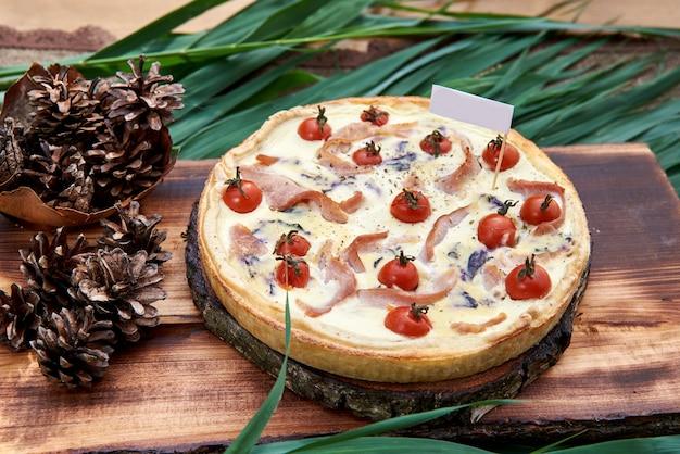 Konzept der französischen und italienischen küche. kuchen mit gemüse und speck. kirschtomaten, zwiebeln, speck und gewürze auf einem holztisch