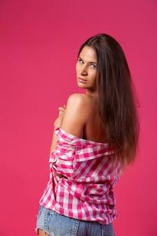 Konzept der fröhlichen sommerstimmung, -entspannung und -schönheit. nahaufnahme einer schönen frau in den kurzen attraktiven jeans, rosafarbene hemdaufstellung