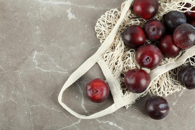 Konzept der früchte mit pflaumen auf grauem strukturiertem tisch.