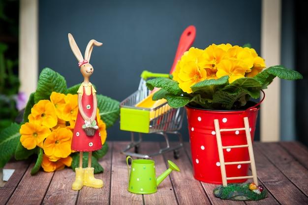 Konzept der gartenarbeit sommer und frühling, harmonie und schönheit. blumen primula gelb und gartengeräte. helles foto im cartoon-stil