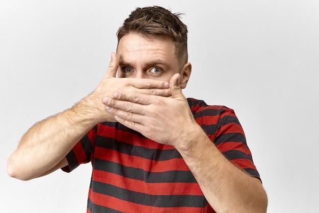 Konzept der geheimhaltung und angst. isolierte ansicht eines mysteriösen jungen mannes in gestreiftem t-shirt, der seinen mund bedeckt, verboten zu sprechen, keine vertraulichen informationen oder geheimnisse preisgeben darf, eingeschüchtert