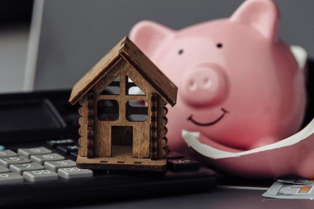 Konzept der geldersparnis für ein neues haus. gebrochenes sparschwein mit taschenrechner und holzhaus. nahaufnahme
