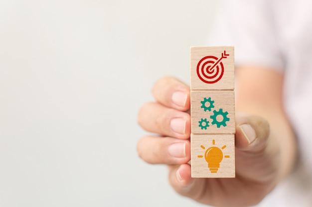 Konzept der geschäftsstrategie und des aktionsplans. hand, die den hölzernen würfelblock stapelt mit ikone hält