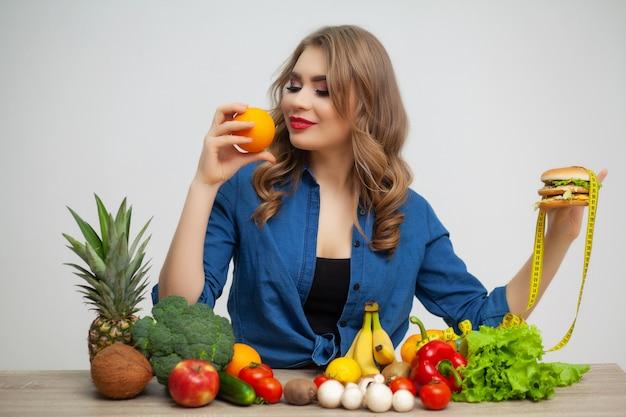 Konzept der gesunden ernährung, burger mit gelbem maßband und orange.