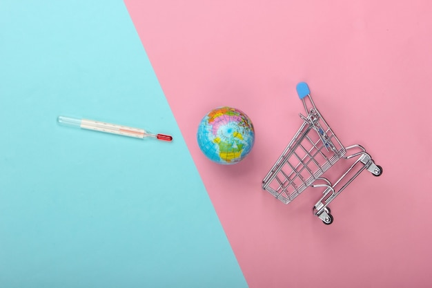 Konzept der globalen erwärmung. einkaufswagen mit thermometer und globus auf blau-rosa pastellhintergrund. draufsicht, minimalismus
