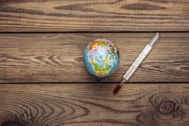 Konzept der globalen erwärmung. globus mit thermometer auf einem holz