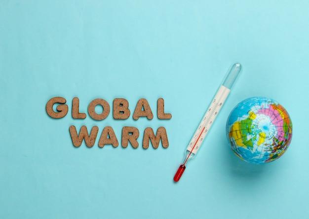 Konzept der globalen erwärmung. globus und thermometer auf blau