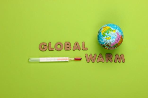 Konzept der globalen erwärmung. globus und thermometer auf grün